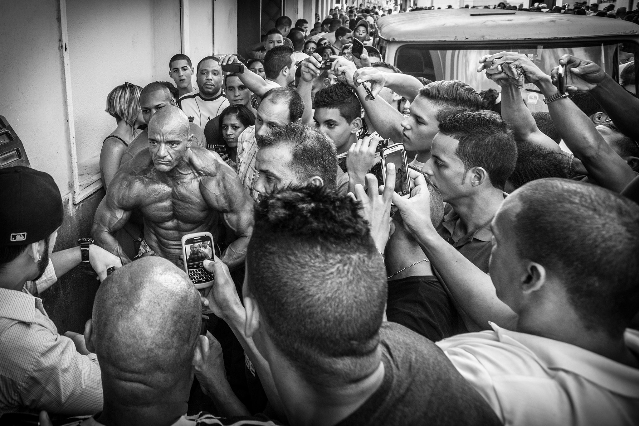 Picture of a crowd surrounding a competitor from the bodybuilding competition, taking pictures with their cell phones while he flexes Photo by Arien Chang via National Geographic PROOF