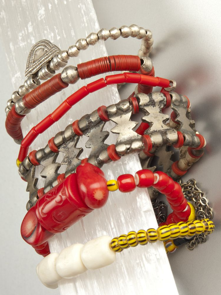 Red bracelet collection includes red coral (for intuition), protective amulet from Ethiopia, sand cast trade beads from Africa's Ivory Coast, carved white bone, assorted collection of red African tribal beads    Standard 7″  Custom colors and sizing available