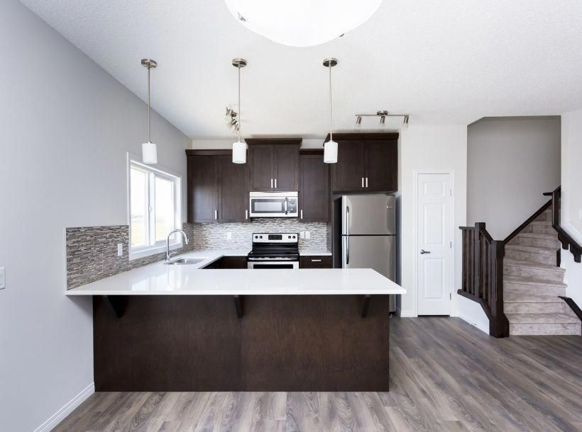 A Beautiful White Kitchen With Dark Brown Cabinets Gray Floors