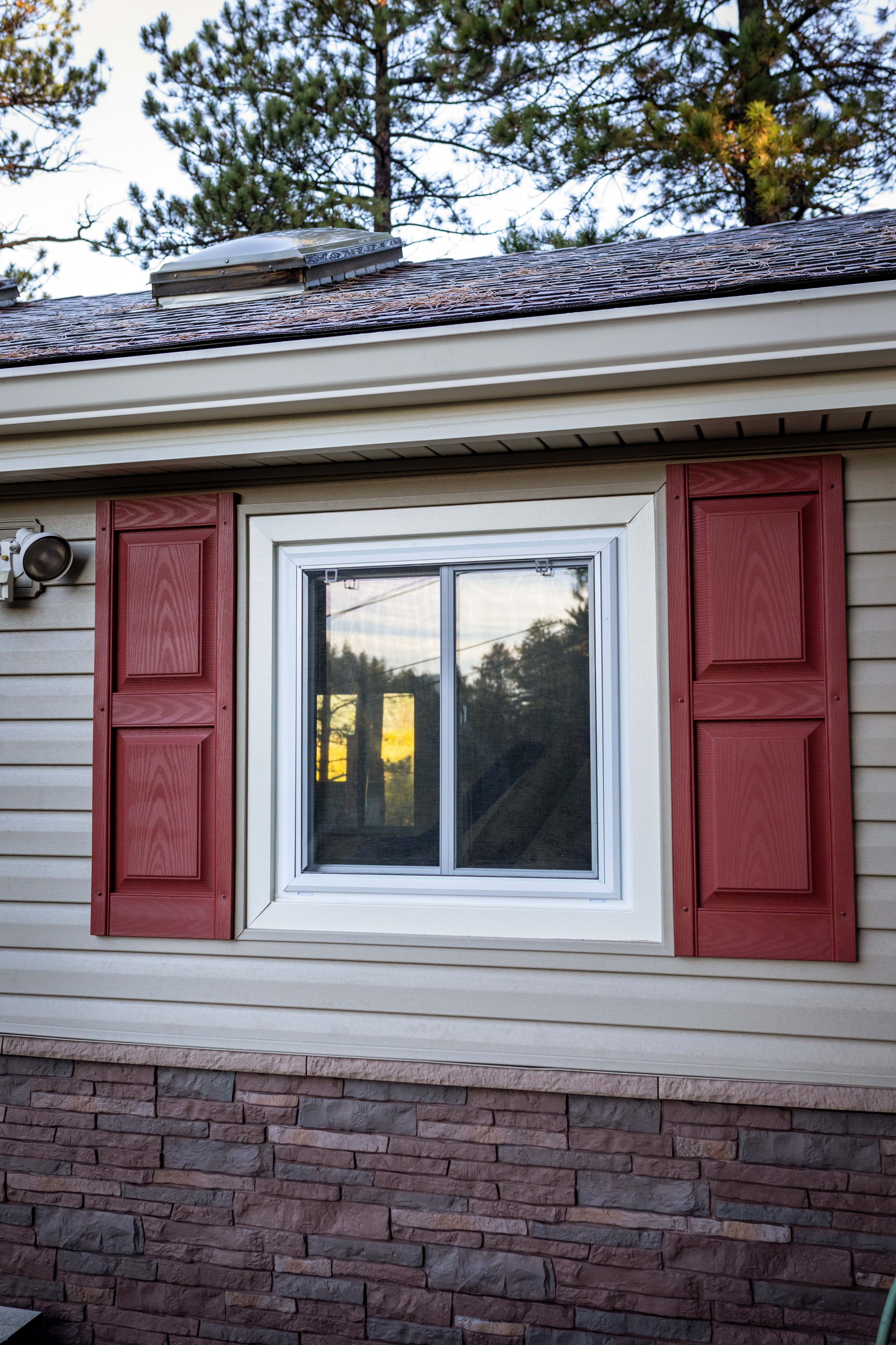 The Red In The Stone Pairs Nicely With The Red Shutters Making The Home Much More Cohesive Windows Stone Windows Red Shutters Home Improvement Contractors