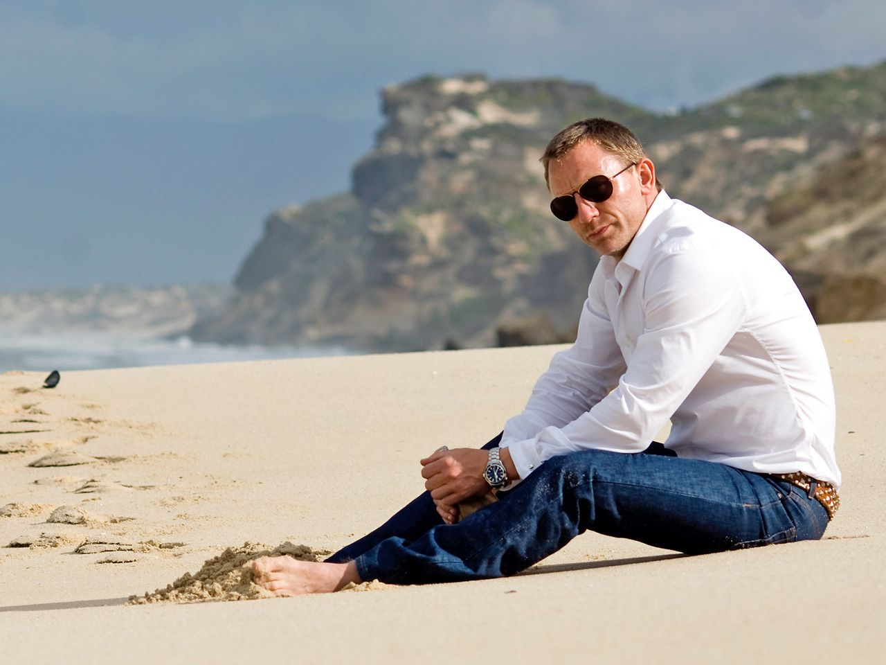 James Bond actor, Daniel Craig at the beach wearing white shirt on jeans. Description from modernmancollection.com. I searched for this on bing.com/images