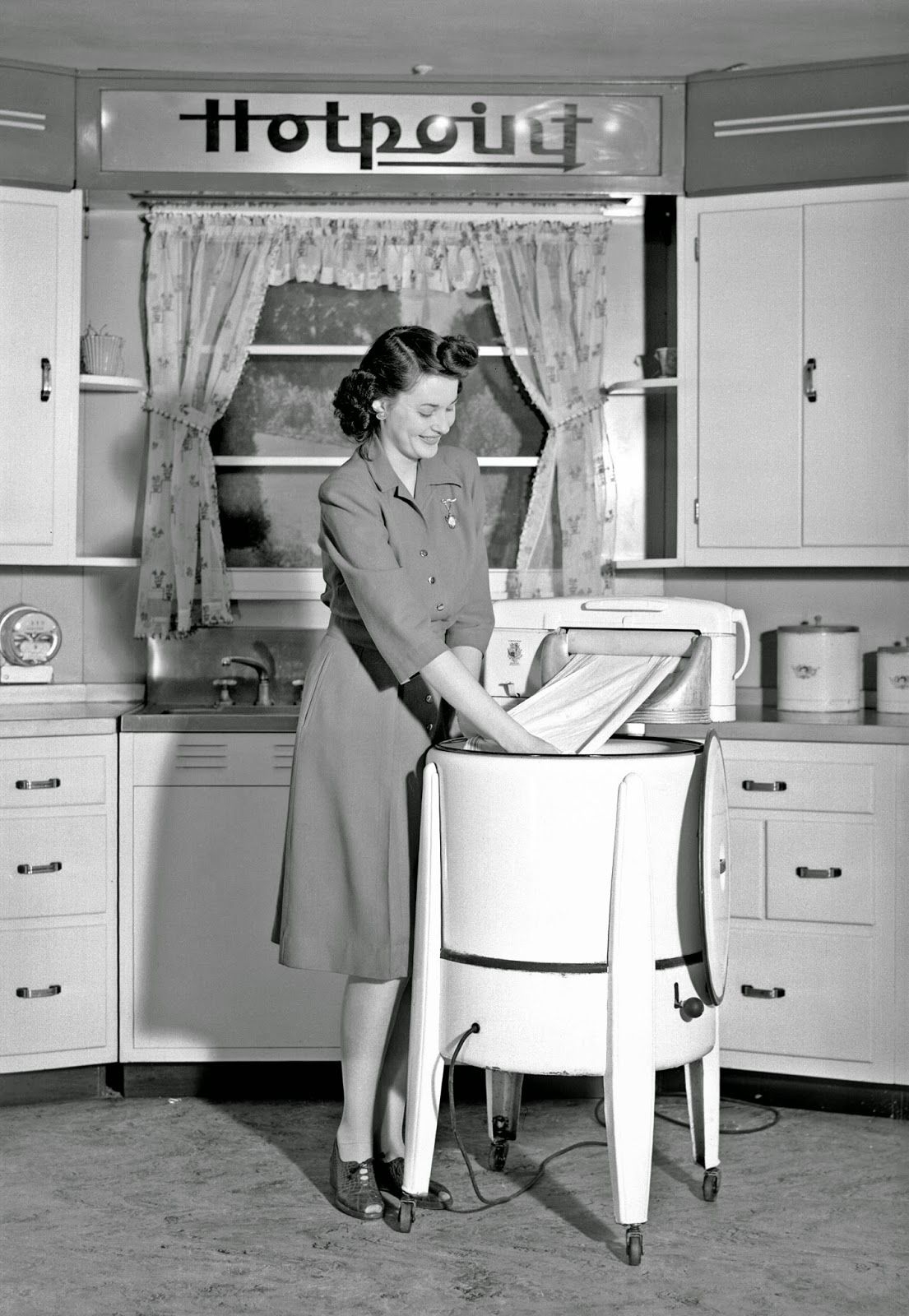 A Woman Demonstrates A Hotpoint Wringer Washing Machine