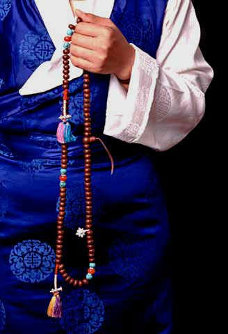 "Tibetan holding a Mala, used for ""counting"" out mantras. Same as Catholics and Muslims, Hmmmm!"