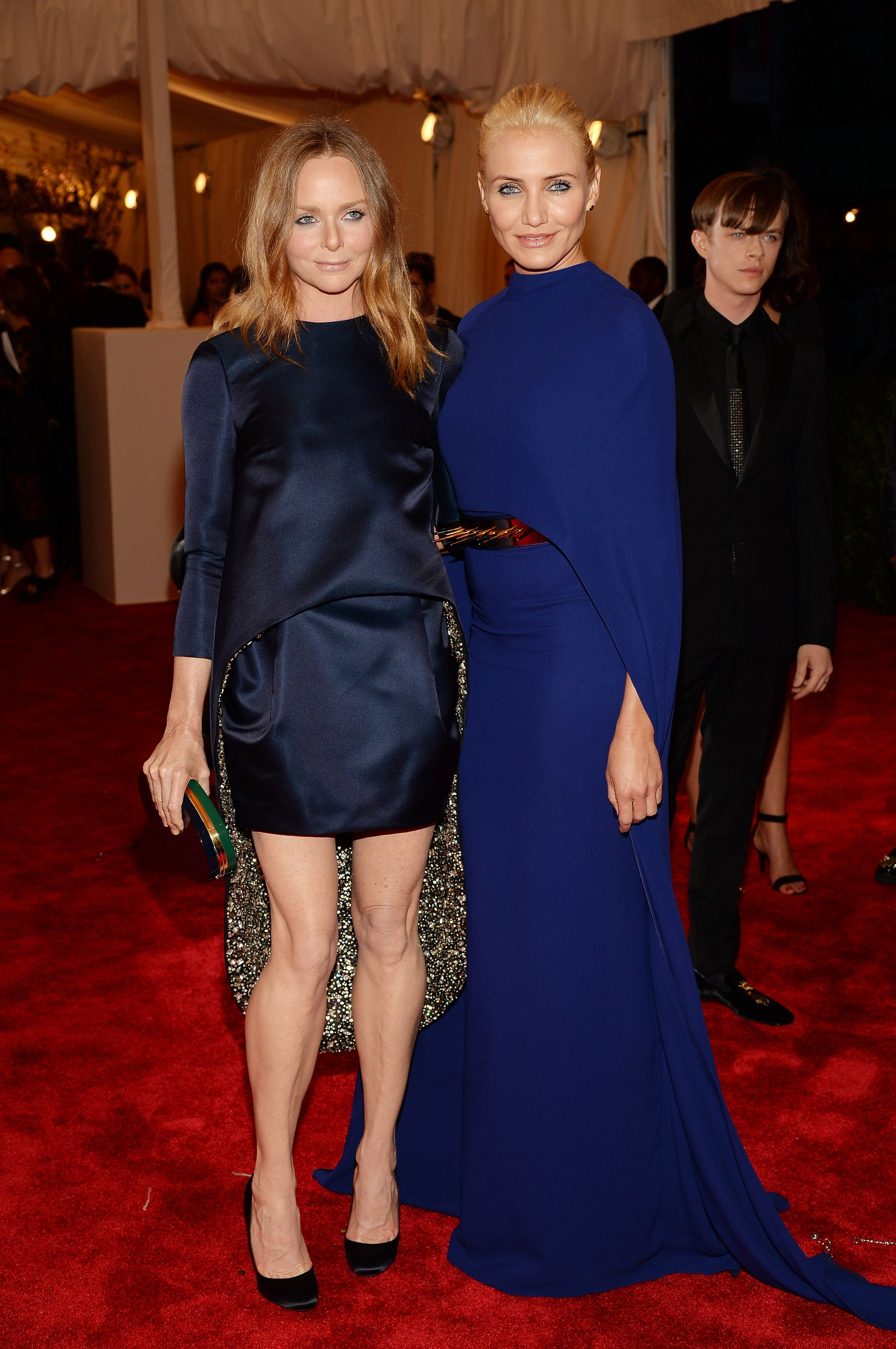 Stella McCartney at the Met Gala in our navy blue satin top with diamond embroidered lining, mini skirt and high heel pumps with green/crème plexi oval clutch.    Cameron Diaz in our blue crepe gown with cape, gold spiked belt, platform stud sandals and wooden box clutch.