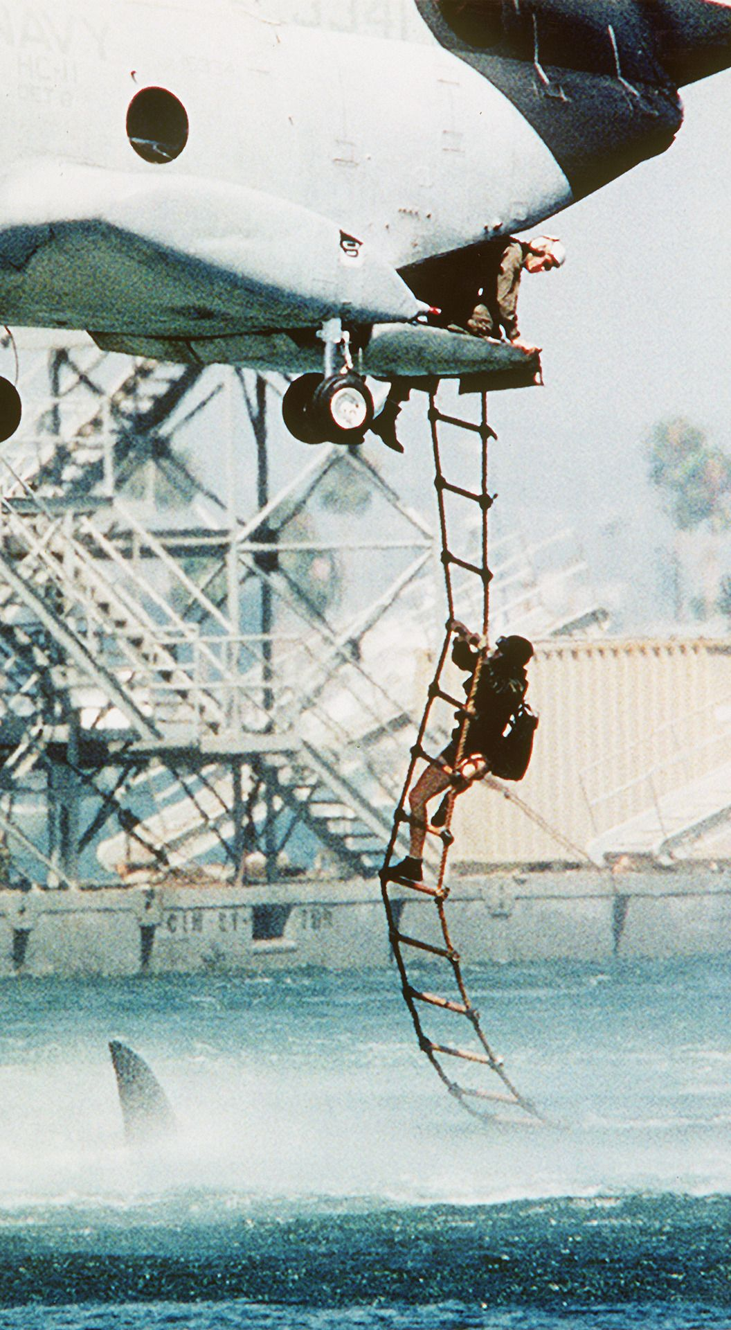 : A soldier grips the rope ladder extended from the rear of a helicopter as a shark fin passes in the water close below.
