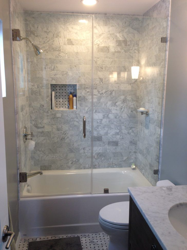 Rectangle white bathtub made from acrylic and glass door connected by grey wall tile also