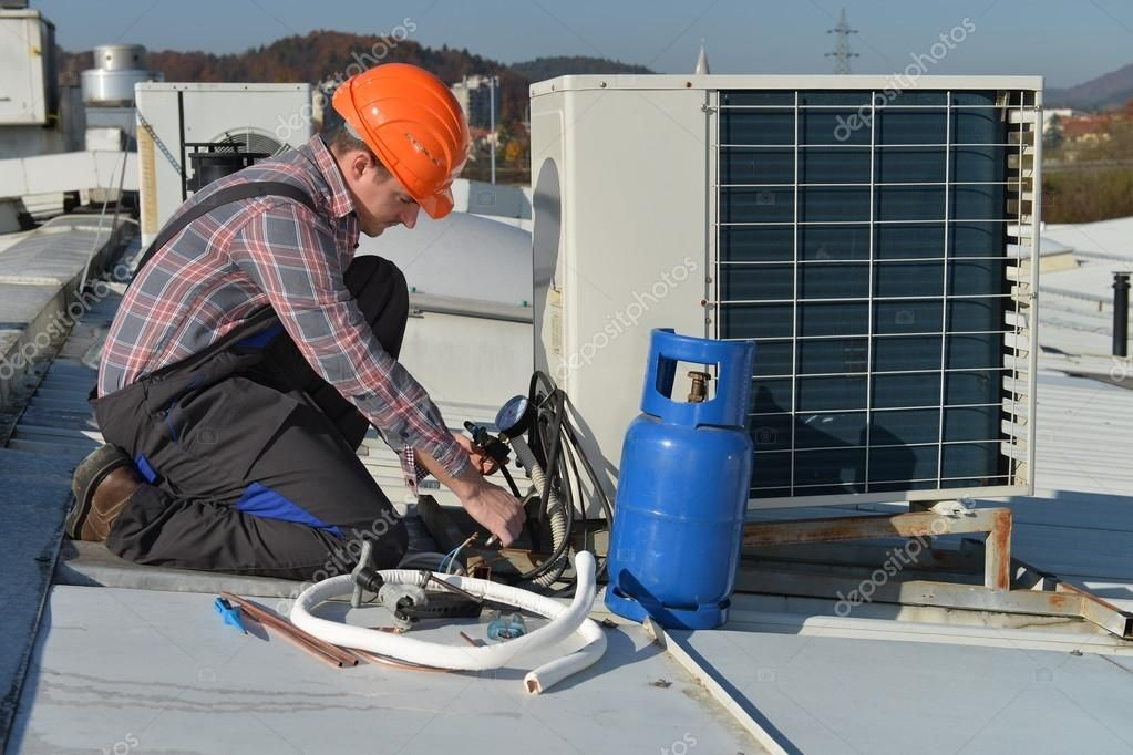 Young repairman fixing air conditioning system Stock