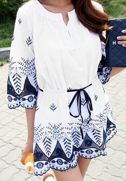 Model in a cute pose wearing embroidered long sleeve tunic and blue pouch