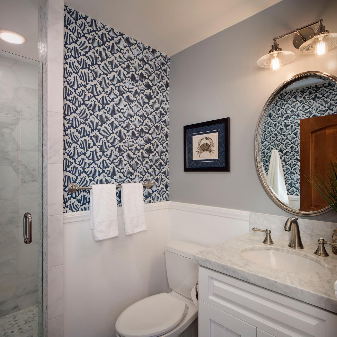photos of remodeled bathrooms%0A Cresting waves make a compelling graphic backdrop in this petite bathroom   Keeping the wallpaper only in select areas of the room keeps the pattern  from