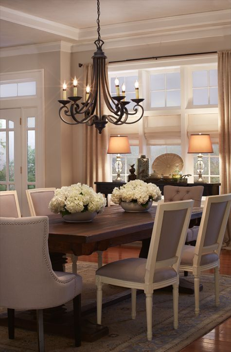 A beautiful dining room restain table new chairs light fixture neutral carpet