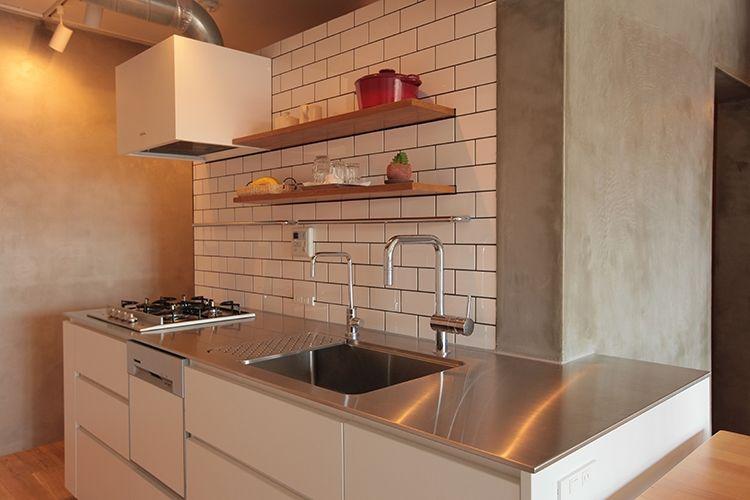 白いキッチンに白いタイルのコンビネーション ステンレスの天板と