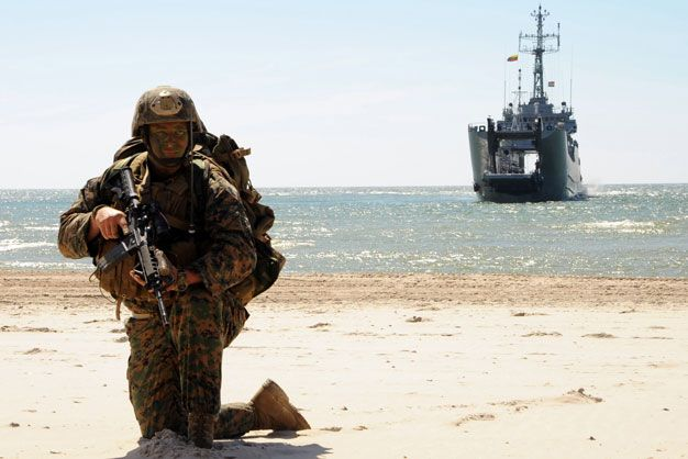 US Marine Corps Sgt Christopher Judy holds position on a beach with