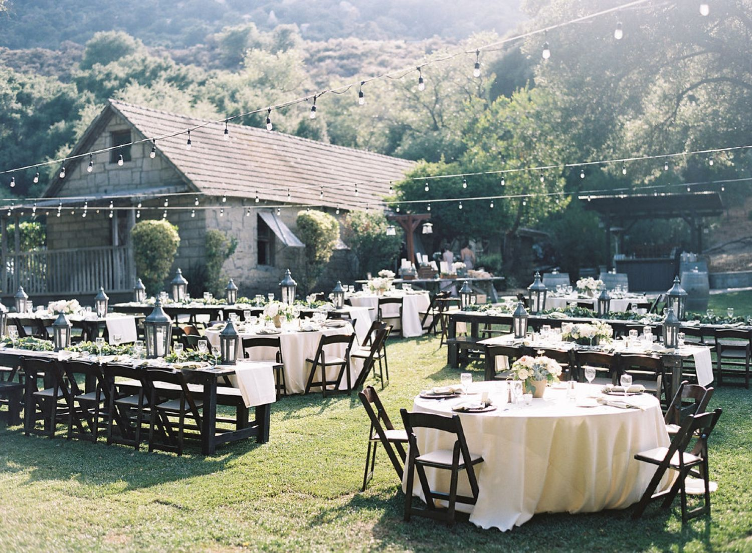 Superbe Twinkle Light Reception With Cream Colored Table Cloths And Dark Chairs