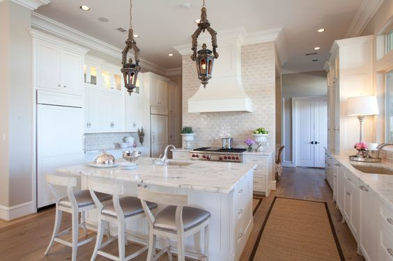 The all-white kitchen exudes a fresh, clean aesthetic.  The homeowners selected honed Calacatta Marble;  backsplash from Walker Zanger;  isl...
