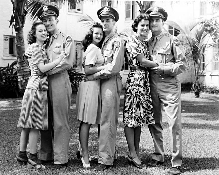 I love that the girl on the left is wearing socks with her sandals!!!  Soldiers and their gals c.1940s