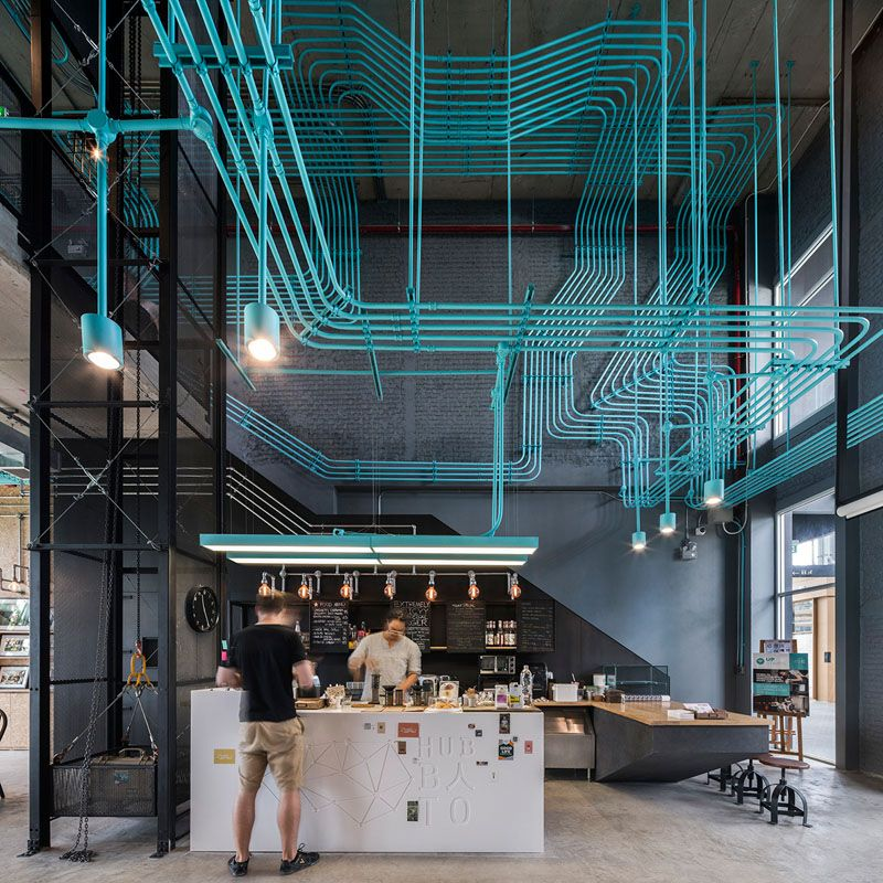 Turquoise electrical conduit is a design feature running through this co-working office space.