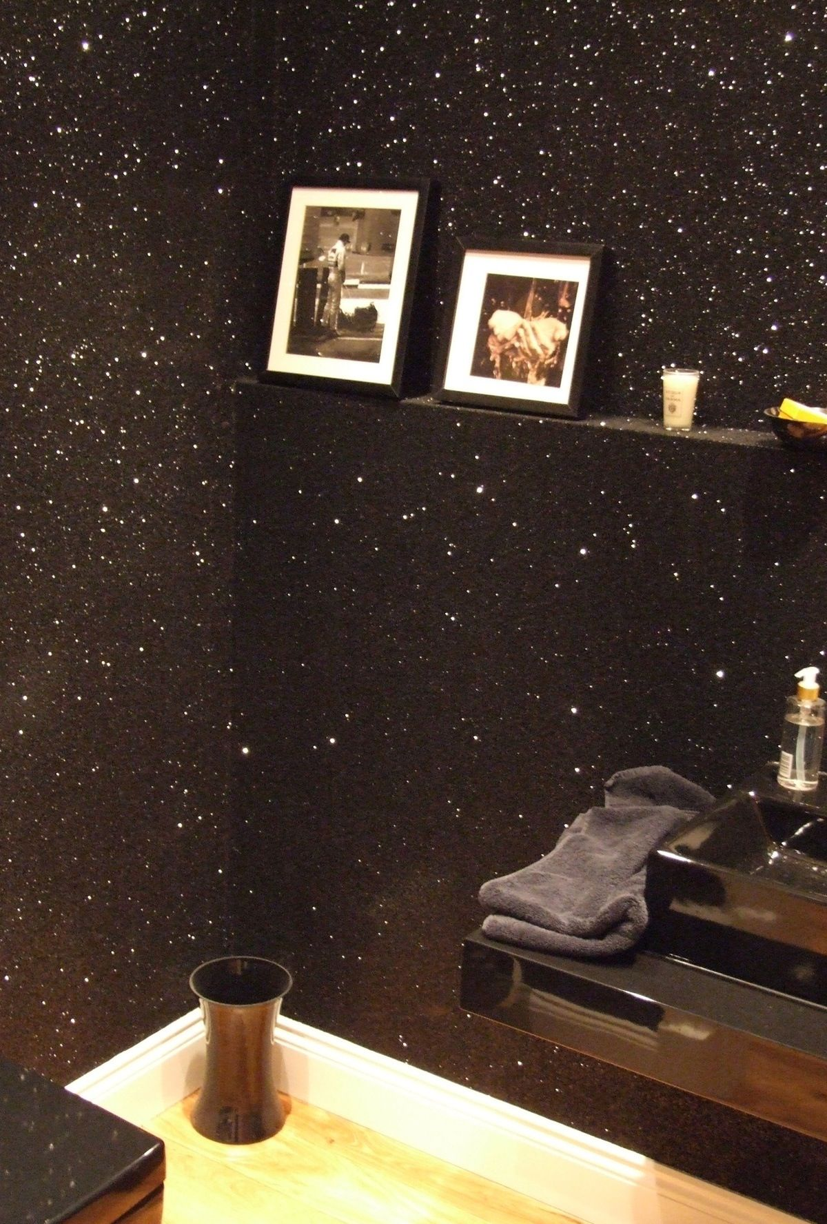 Black sparkle wall cent wall in bedroom behind the bed maybe