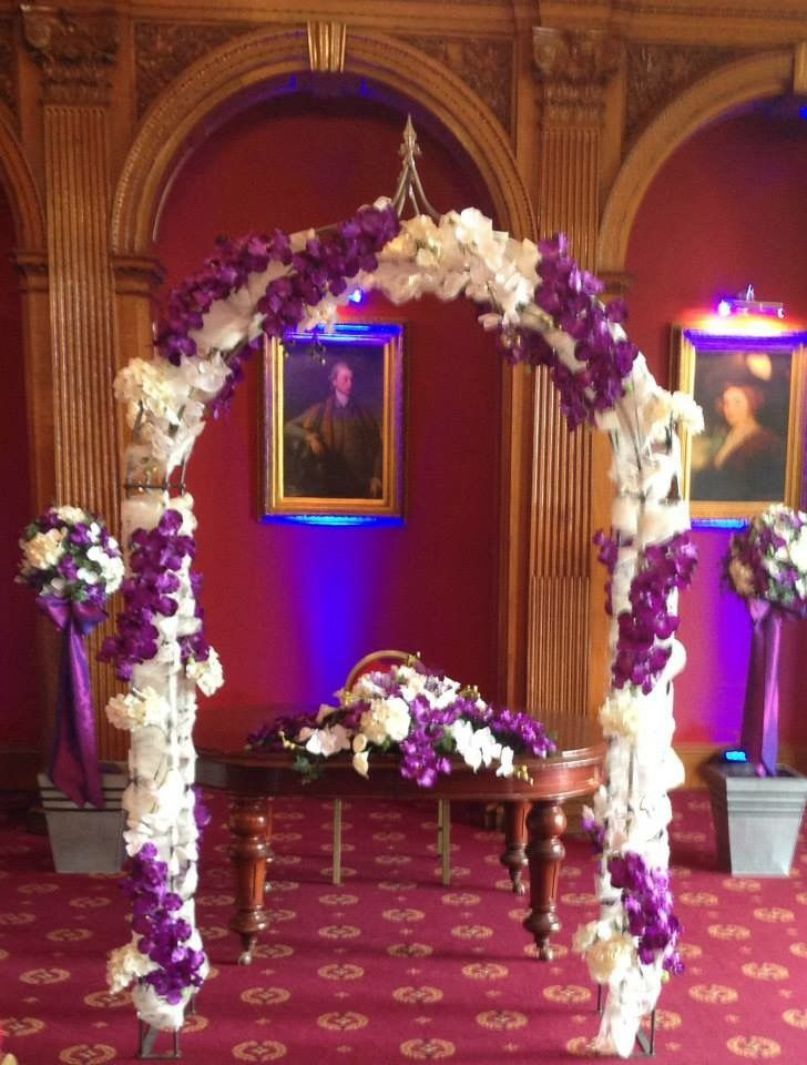 Such a striking wedding ceremony in cadbury purple and ivory. From the bridal arch, to the two topiary trees and the registrars table design. Purple vanda orchids being the main flower throughout. www.am-flowers.co.uk