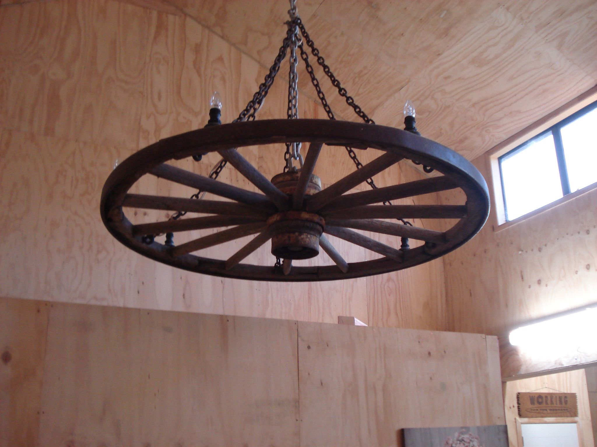 Wagon Wheel Light shines brightly with the plywood room lining