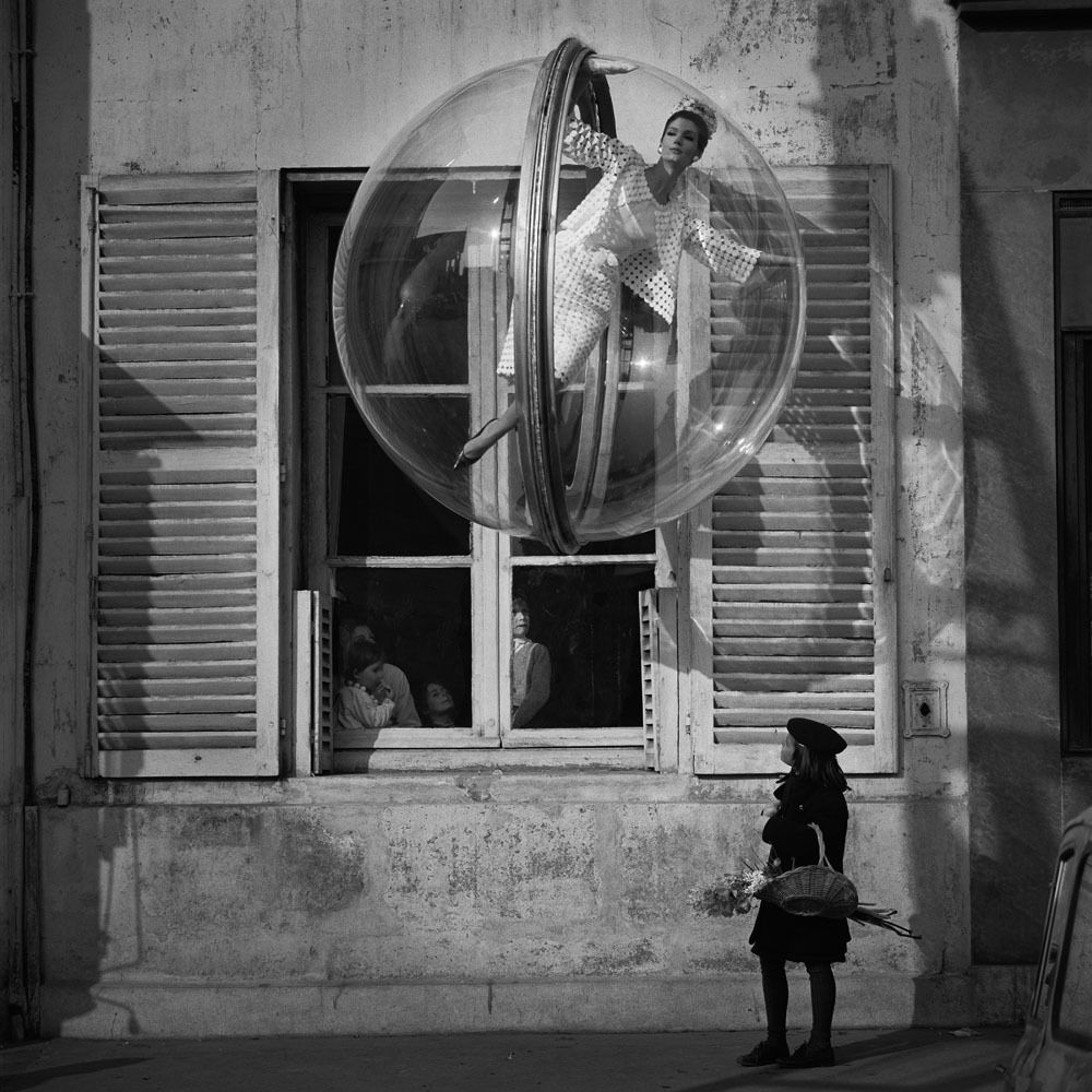 """In 1963 Melvin Sokolsky produced the """"Bubble"""" series of photographs depicting fashion models """"floating"""" in giant clear plastic bubbles suspended in midair above the River Seine in Paris."""