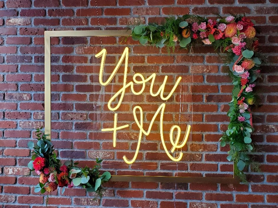 """A """"You and Me"""" sign framed by your custom wedding flowers"""