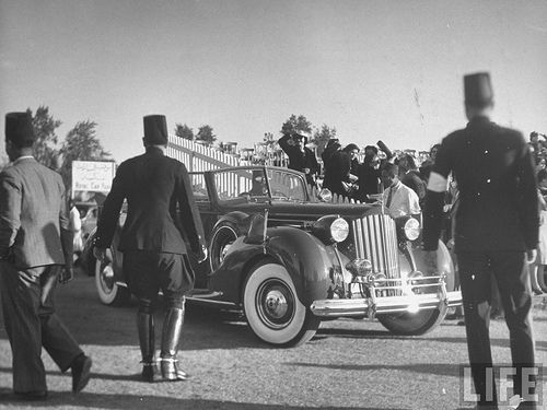 The King arrives in an open car to the Heliopolis Athletic Field during championship soccer match between the Medical & Artillery Units of the Egyptian Army.