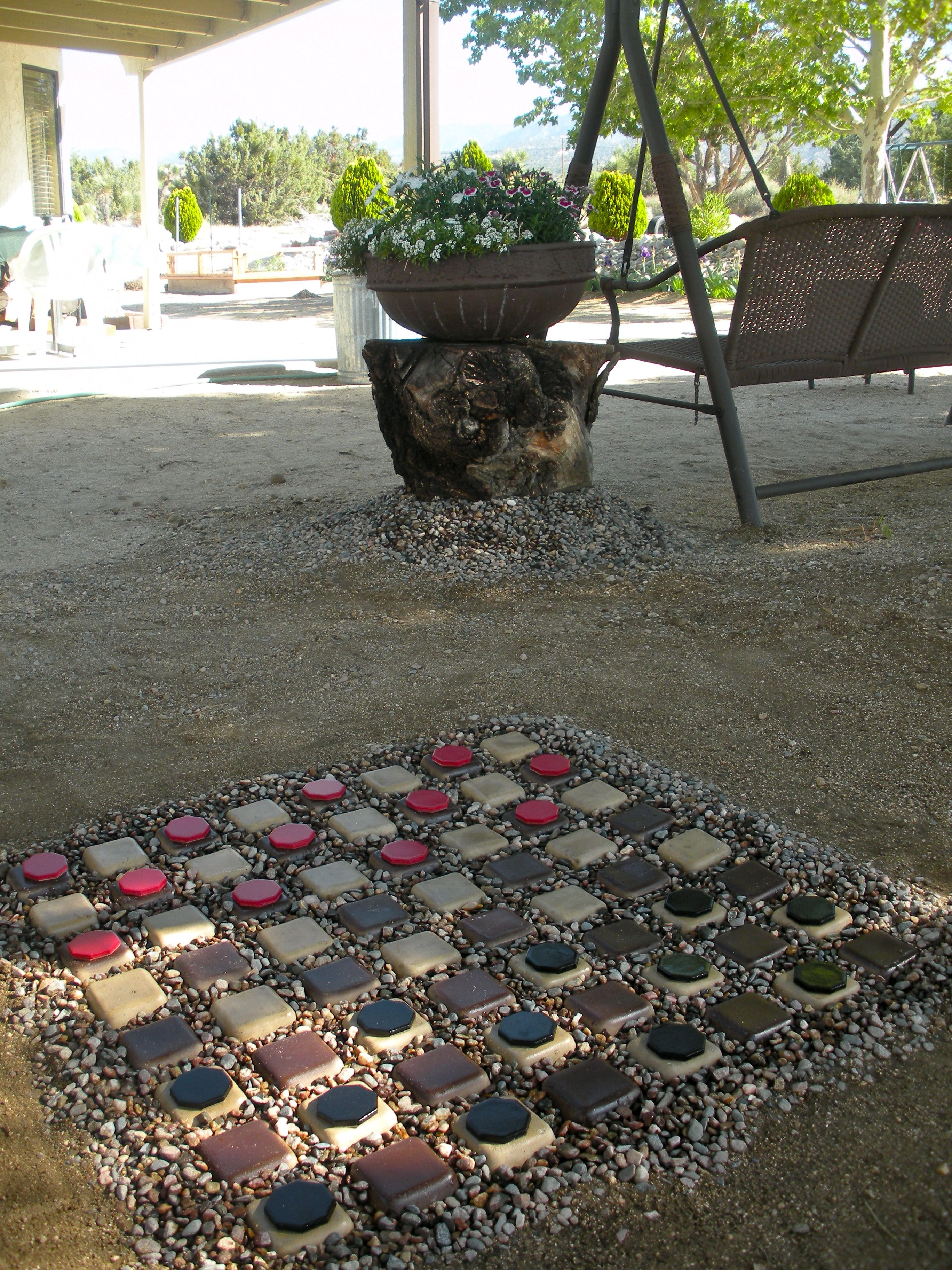 Outdoor checker board made from concrete driveable pavers, pea gravel and tiles.    FUN!