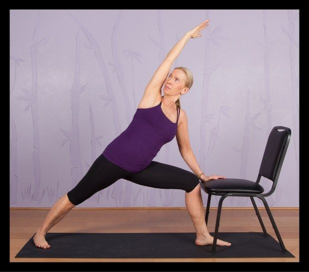 A modified version of the extended side angle yoga pose using a chair.