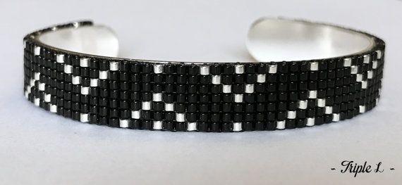 ~ DESCRIPTIF ~ Ce bracelet manchette LINE est composé dun tissage fait main avec des perles de verre Miyuki et dune manchette en laiton argenté. Les perles argentées sont plaquées argent 925. Couleurs des perles : noir - argenté. Dimensions : 1 cm de large. ~ MATERIEL UTILISE ~ - Perles de verre japonaises Miyuki - Manchette en laiton argenté - origine : Italie  ~ ENVOI ~ Les bijoux sont envoyés en courrier suivi dans une enveloppe en papier bulle et soigneusement emballés.  ~ PRECAUTIONS…