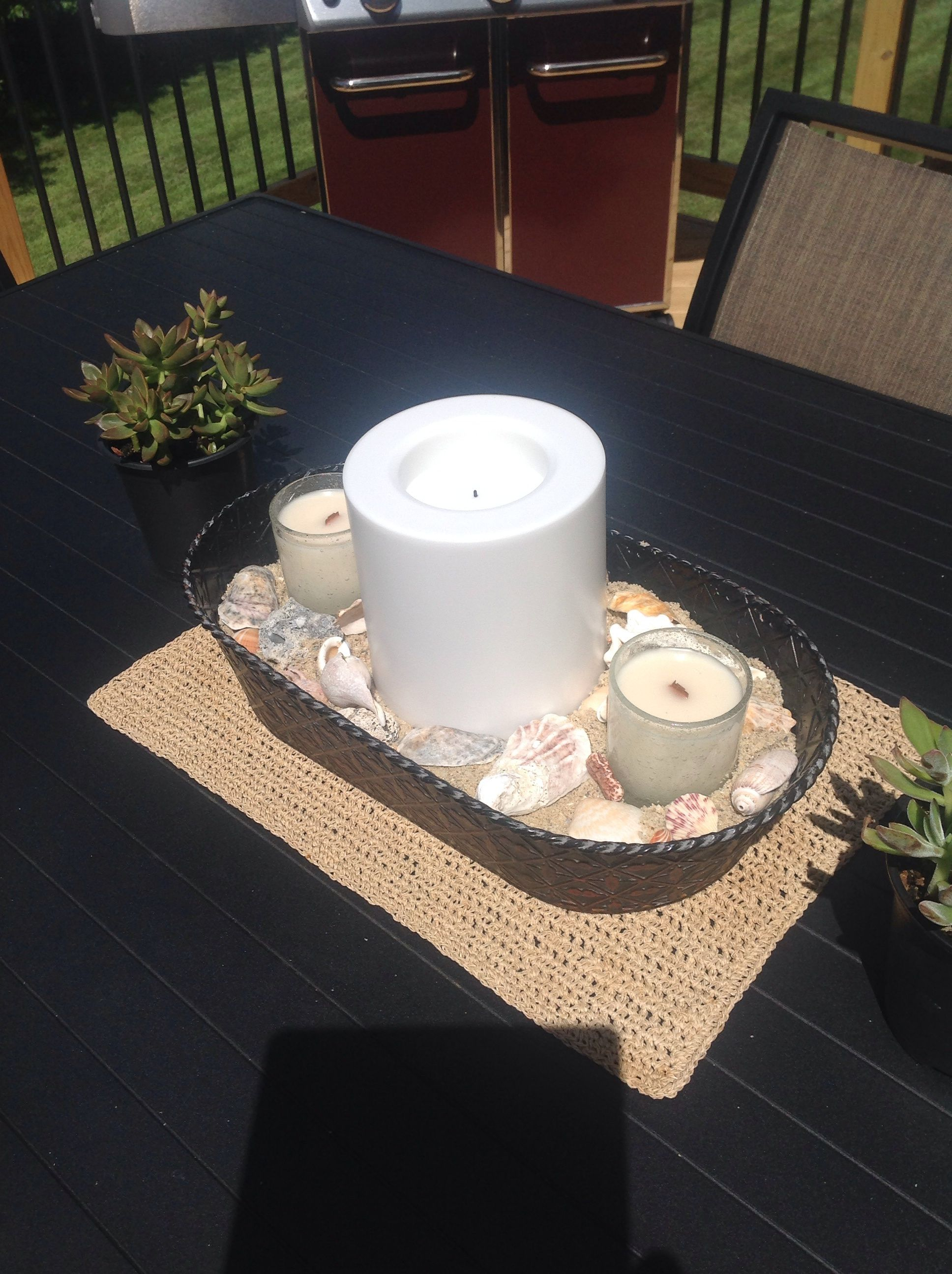 I had this metal container. Added sand along with some shells that we collected over the years and one large LED candle and two small citronella candles.