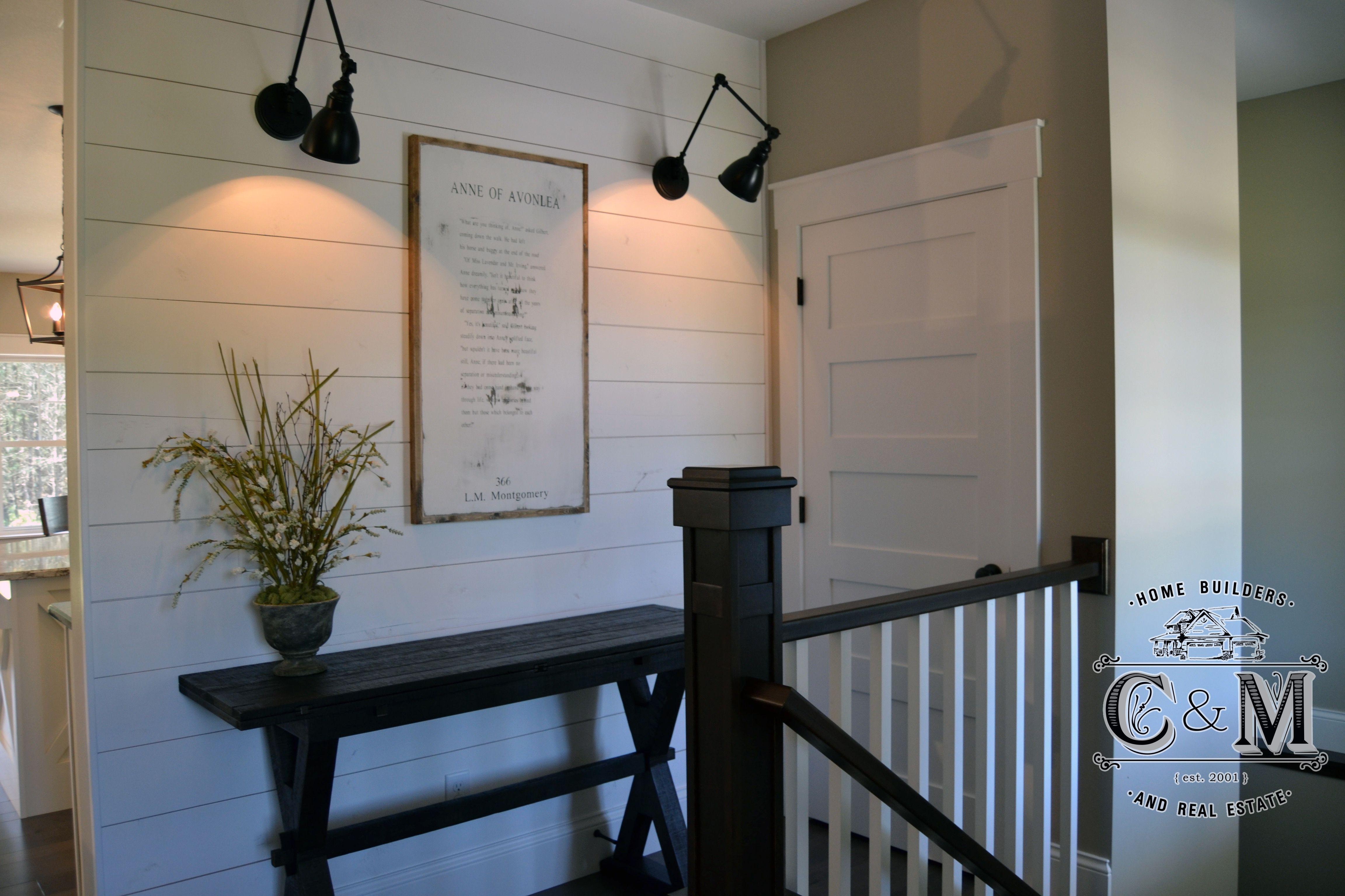 Wall featuring industrial light fixtures makes for a country feel when walking into this entry way cm home builders and real estate eau claire wi