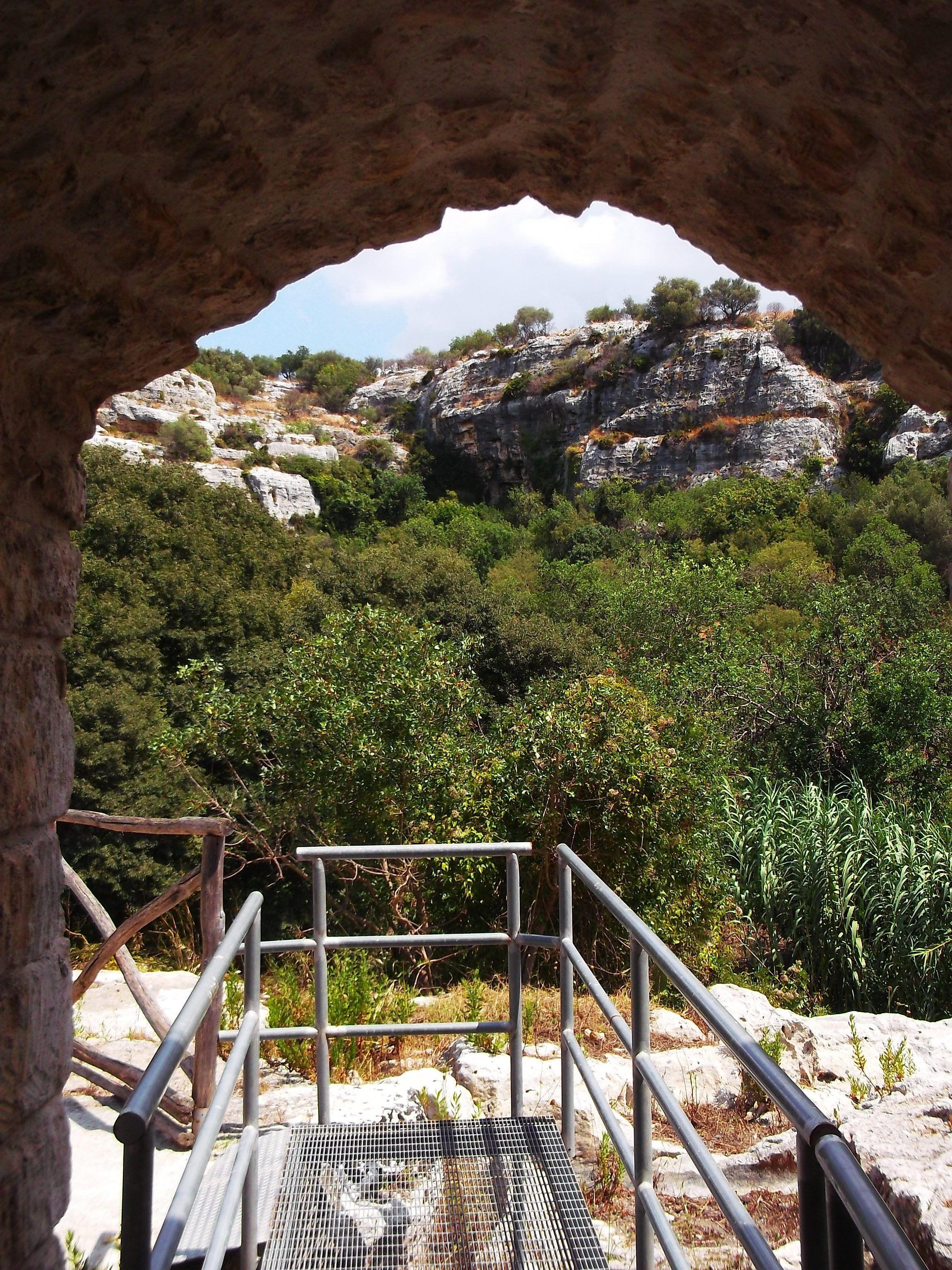 """Ispica (RG) - Ingresso alla spettacolare Cava di Ispica, un tortuoso taglio naturale tra rocce calcaree e vegetazione rigogliosa - Acces to Cava Ispica, """"cava"""" is a false friend of """"cave"""", in Sicily the term """"cava"""" is like """"canyon""""."""