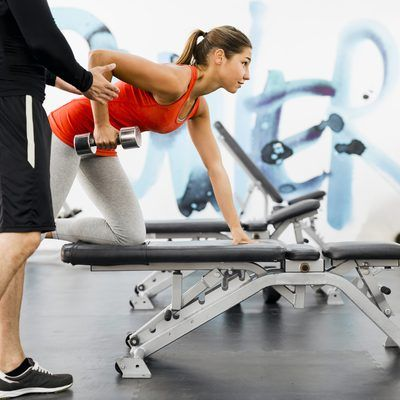 personal trainer working with a client in the gym doing