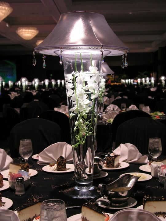Lit lampshade over trumpet vase with submerged florals