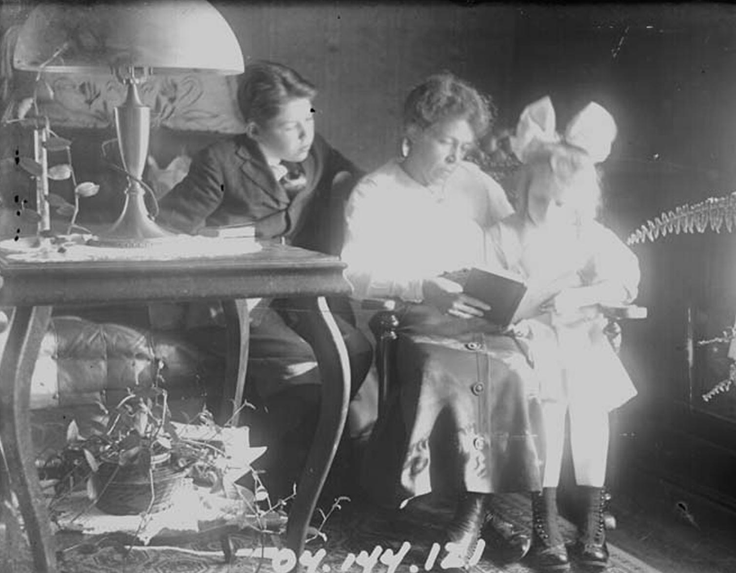 Satie Draper reading to her children Winnie and Merrell, c. 1920.  Satie's husband, Charles Draper, is the photographer.