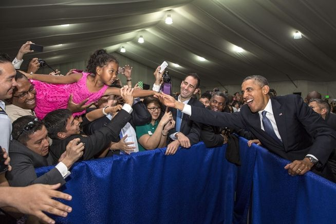 President barack obama stretches to shake the hand of a young girl president barack obama stretches to shake the hand of a young girl held aloft during a u embassy meet and greet at the sofitel hotel in manila philippines m4hsunfo Image collections