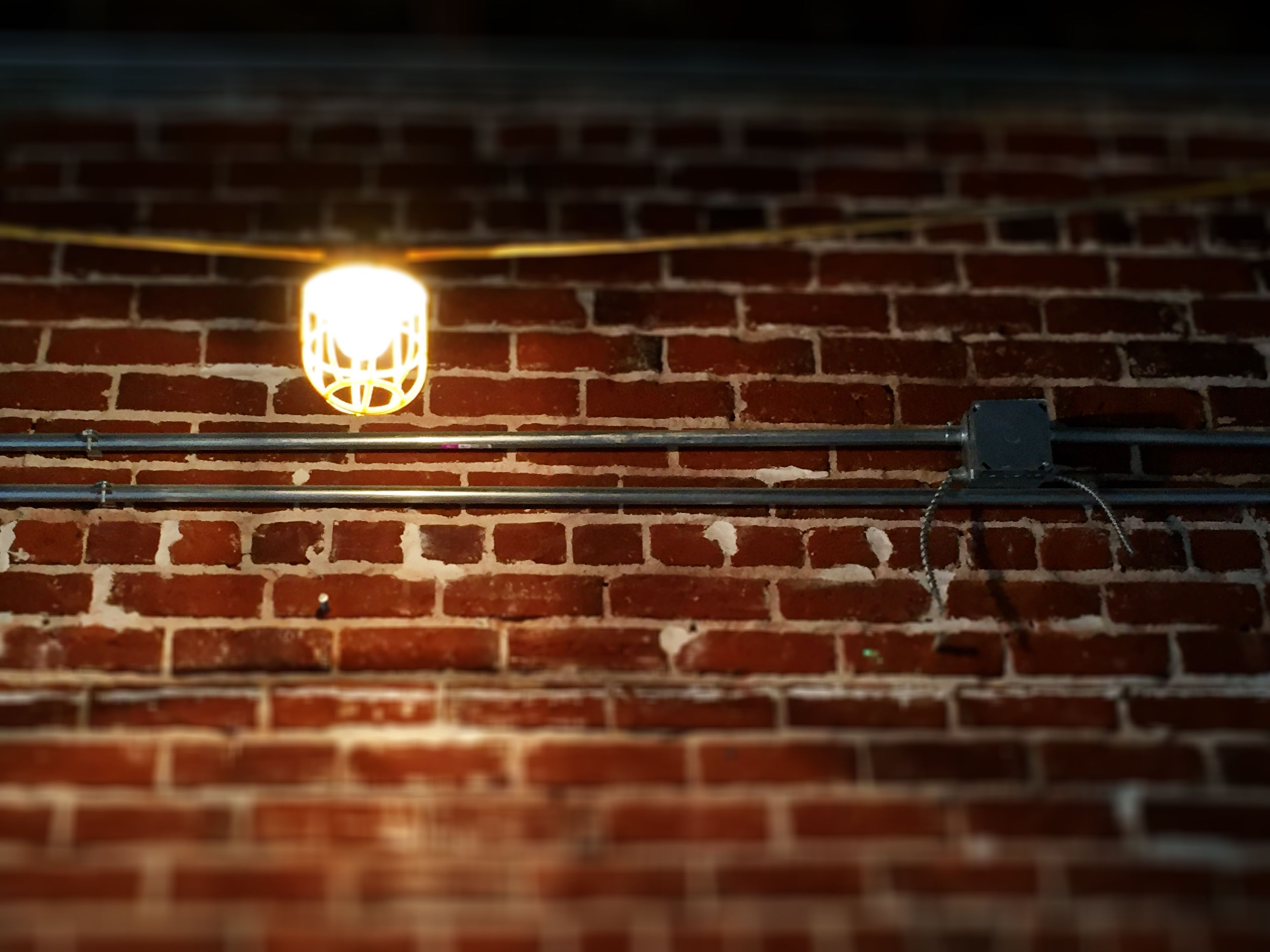 Pretty little work light shines brightly against the #brick at The #Bar. @Morgans_On_Main #construction #visitwoodland #visityolo