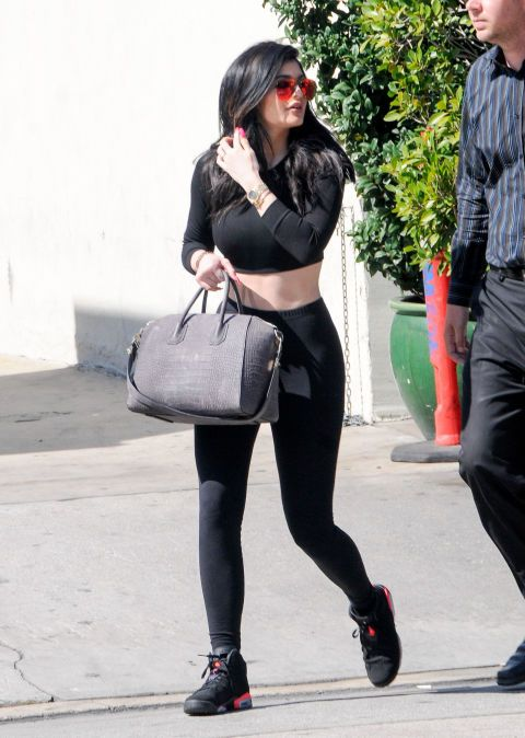 d45c83b8cb1 Kylie s red sunglasses and pink nails pop against this simple black crop  top and legging combo.