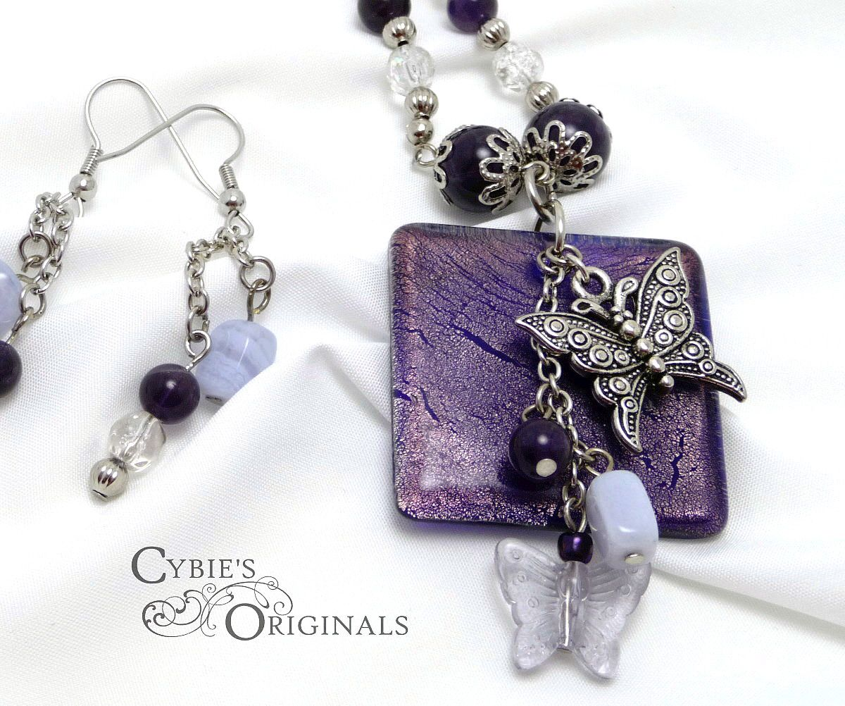 "Dark Amethyst and Blue lace agate semi-precious stones with butterfly pendant and silver accents. Includes matching earrings.  Necklace is approximately 23"" in length."