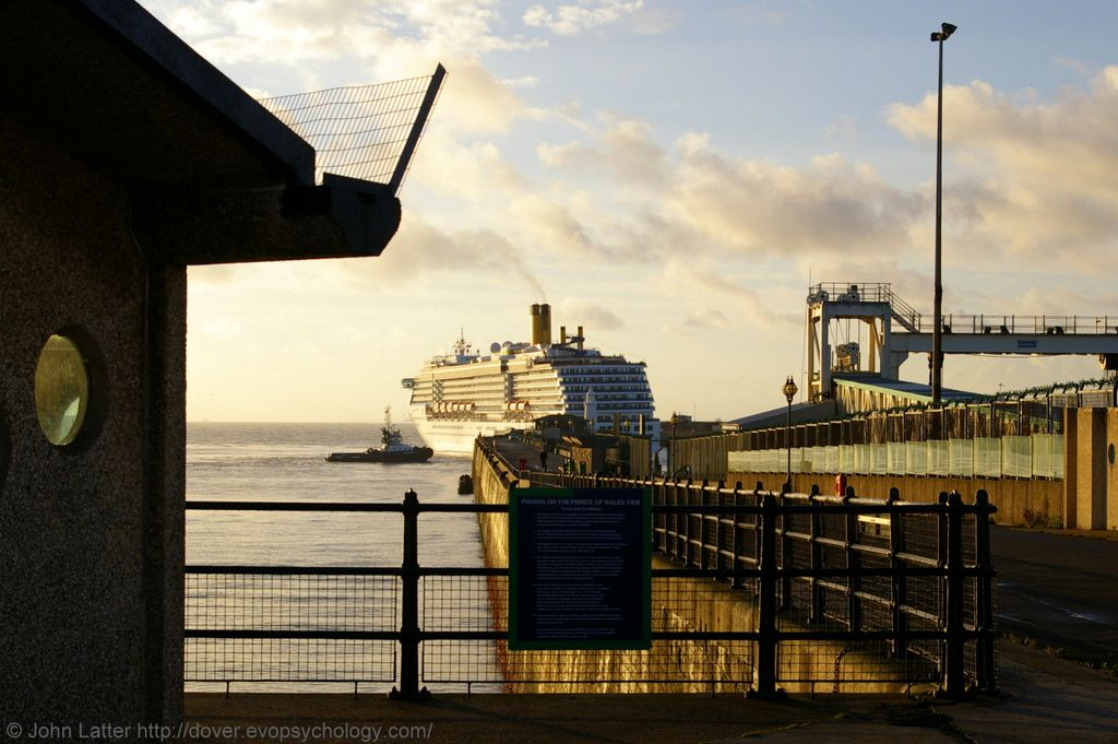 Prince of Wales Pier and MS Costa Atlantica Cruise Ship at Daybreak, Dover Harbour, Kent, England, United Kingdom. Behind the light tower (right) is the ex-Jetfoil Terminal on the Hoverport Apron. At the stern of the passenger ship is the Harbour View Cafe and lighthouse. Vessel owned by Costa Cruises, DHB Dauntless tug owned by Dover Harbour Board. View from Northern Porthole Shelters. 2010 Port of Dover, Sunrise, Travel, Tourism, and Vacation photo. See…