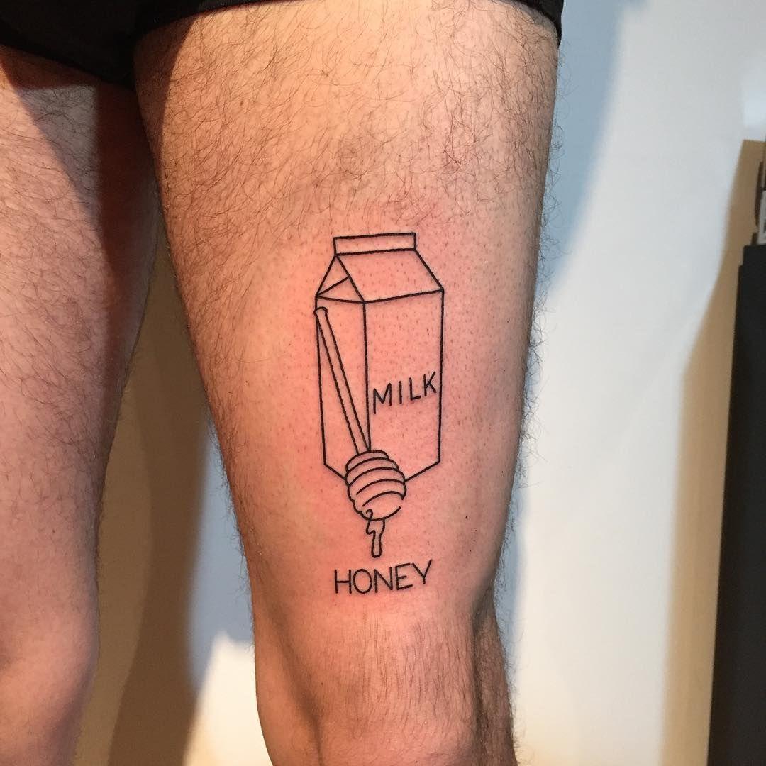 Milk and honey tattoo on the left thigh stick tattoo