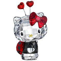 Hello Kitty Ladybug hecho en cristal de Swarovski  Hello Kitty se viste para la primavera con su bonito traje de mariquita. La pieza brilla en cristal transparente y Black Diamond con los bigotes impresos en negro. Su lazo divertido, los corazones y el traje de mariquita resplandecen con intensidad en cristal Light Siam.