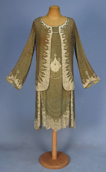 Circa 1922 ensemble: sleeveless sage green cotton voile dress having an allover pattern of serpentine crystal beads, large Arabesque devices in pearlescent white beads with eyelets above a scalloped dropped waist, flared skirt in four panels with heavy beading and eyelets. Matching long sleeve jacket with cut work and eyelet trim.