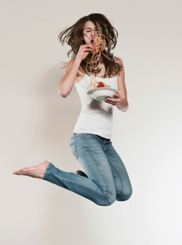 Stock Photo : Teenage girl (16-17) jumping and eating noodles