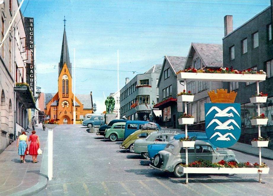 Haugesund i Rogaland fylke. 1950-tallet. Kirke, biler, 2 damer i gata og byvåpen.