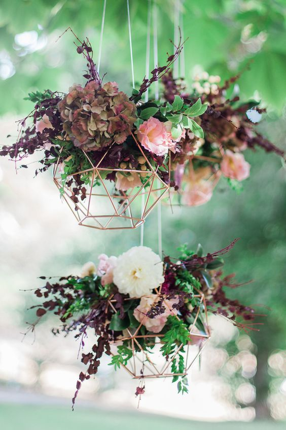 Geometric copper wedding reception hanging feature with burgundy flowers via Blush & Mint Photography