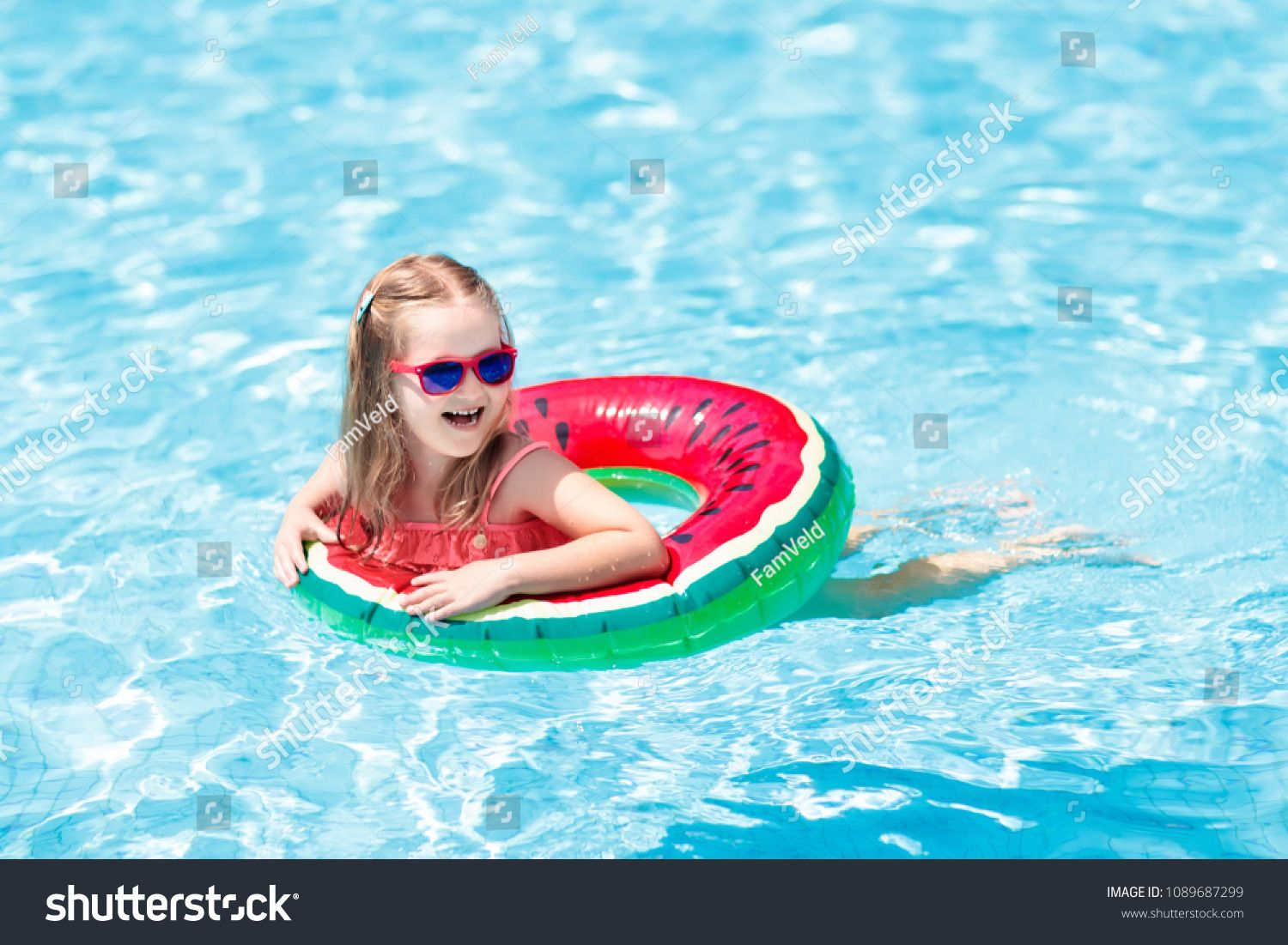 Child with watermelon inflatable ring in swimming pool