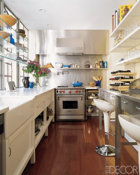 This kitchen of a Manhattan townhouse features Carrara-marble counters and a custom-made stainless-steel hood and storage unit.