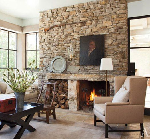 Natural stone fireplace. Like the mix of contemporary furniture and antique accessories.