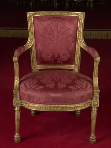 Located 2015 in the Music Room of Buckingham Palace, London, UK. Gilt Beechwood & Silk Damask Set of Elbow Chairs made by Georges Jacob. 29 Chairs Carved & Gilded, Curved upholstered back within bead, husk & leaf borders. Scrolled padded arms with Leaf carving. Tapering front legs & back legs splayed. Bought by George IV (1762-1830) UK Uncle of Queen Victoria (1819-1901) UK.
